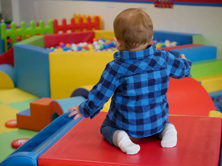 toddler kneeling in a colourful play area